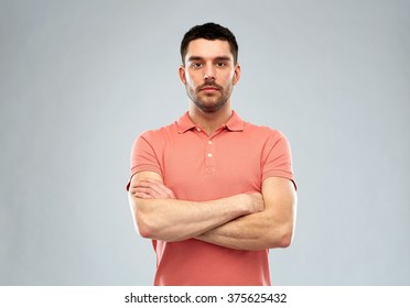 people concept - serious young man in polo t-shirt with crossed arms over gray background