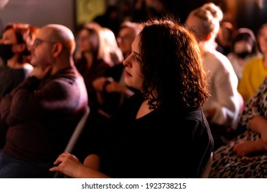 people at the concert. people sit in the auditorium listening to live music