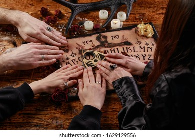 People conducting a seance using a Ouija Board, or Talking Spirit Board, with white candles. Shot from overhead. Occultism.