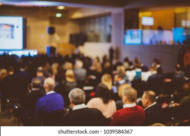 People at conference hall, rear view. Speaker at Business Conference and Presentation. Audience at the conference hall. Abstract blurred photo of conference hall.vintage photo processing