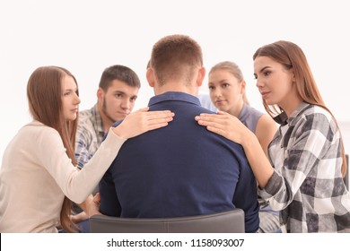 People consoling young man at group therapy session