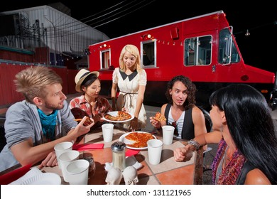 People in conversation while eating pizza from food truck
