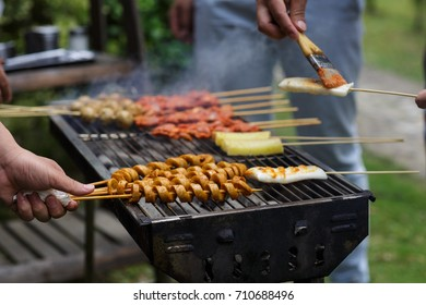people cook shish kebabs from chicken, pork, hot dogs, rice cakes on the street