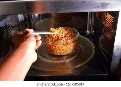 People cooking instant noodle in microwave oven.