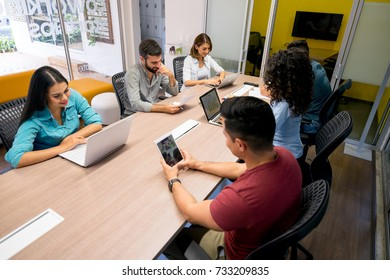 People co-working at an office with their laptops, tablets and documents all looking happy and focused