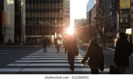 People cross the road with beautiful morning light. Tokyo, Japan. - Feb 25, 2017.