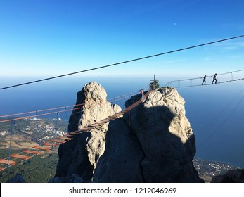 People crossing the chasm on the hanging bridge