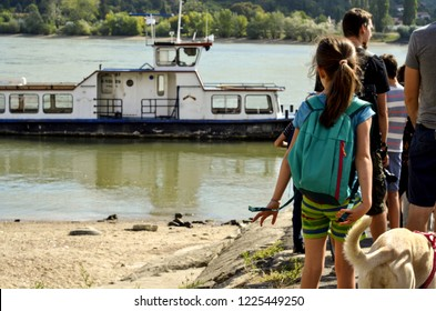 People crossing Danube river by ferry on a summer day in Visegrad, Hungary