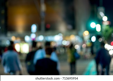The People Crossing the Intersection at Night in the City of Los Angeles; Blur Background with Bokeh Effects