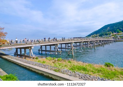 People crossing the Oi River on Togetsukyo Bridge in Arashiyama, Japan.
