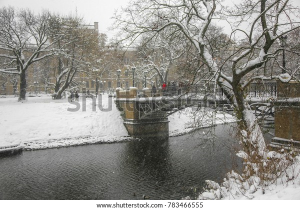 People crossing an old bridge in the city park, in a snowstorm. Riga, Latvia