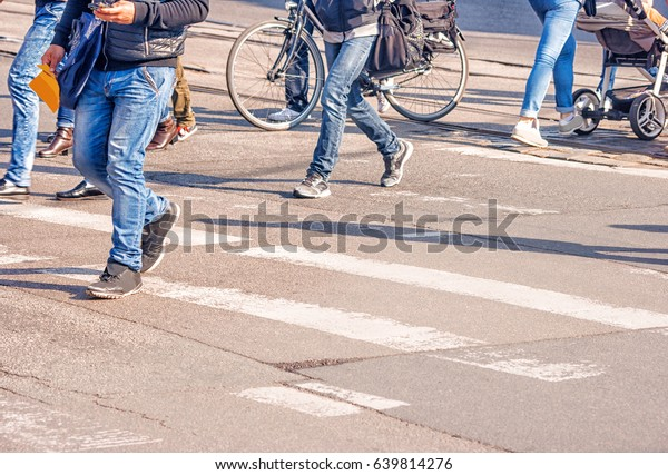 people crossing the pedestrian crossing on sunny spring day