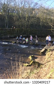 People crossing the river by stepping from stone to stone, in Uppermill. The usual way to cross here, especially on a lovely spring day.