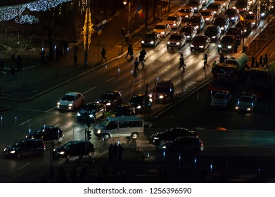 People crossing the street in a busy junction on a December late evening as seen from a high vantage point.