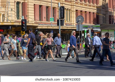 people are crossing street in front of Flinders train station building in Melbourne, Australia: 10/04/18