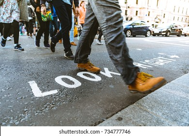 People crossing the street in London, feet close up with the look right writing on the asphalt. Travel and lifestyle concepts.