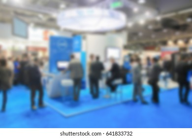 People crowd visit a trade show. Background with an intentional blur effect applied. Location and humans not recognizable.