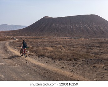 People cycling on a dirt path in the island of La Graciosa, Lanzarote, Canary Islands. Spain. In the background El risco, the mountainous part to the north of Lanzarote