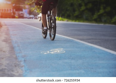 People are cycling on highways with dedicated bicycle lanes and soft light from the front, safe driving, cyclists on bike trails, Cycling for health, Exercise with cycling, Bike, Bycicle.