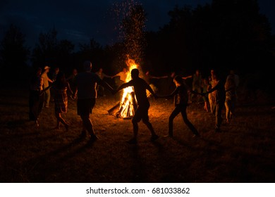 People dance around the campfire. People dance around the fire at night.