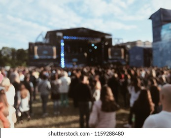 People dance at the music festival in the afternoon. Photo of crowd with raised up hands at music festival, audience applauding to musician band, music festival, happy youth. blurred photo