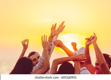 people dancing at the beach with hands up. concept about party, music and people