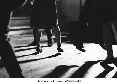 People dancing in the lights of a dance floor during a wedding. Black and white photo.