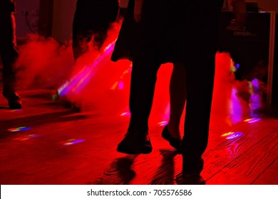 People dancing in the red light and smoke of a wedding party.