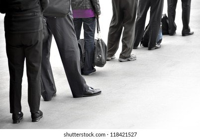 People in dark clothes with bags waiting in queue