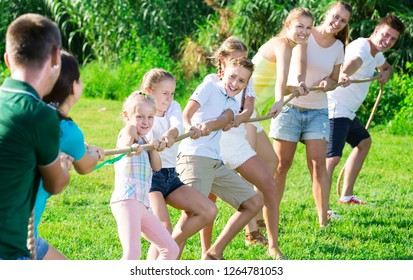people of different ages playing active games in summer park, tugging war