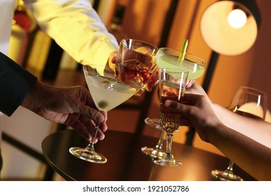 People with different alcohol drinks clinking glasses indoors, closeup