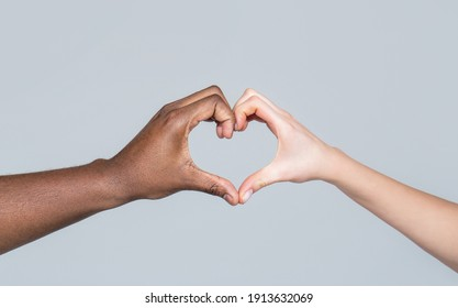 People different skin colors put their hands together making heart shape in white background. Charity, love and diversity - closeup of female and male hands of different skin color making heart shape
