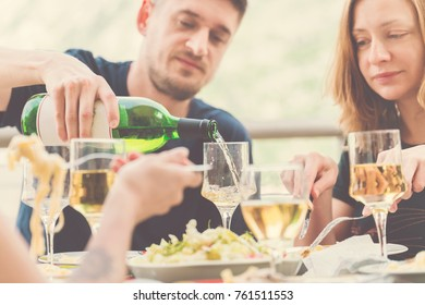 People dine and drink wine on the terrace in the sunlight. Toned