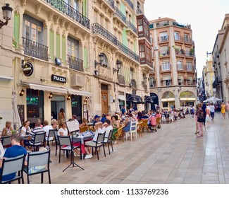 People dining in the evening outdoors in  La Piazza, a Spanish restaurant in Alicante city. Costa Brava Spain, Europe. July 2018