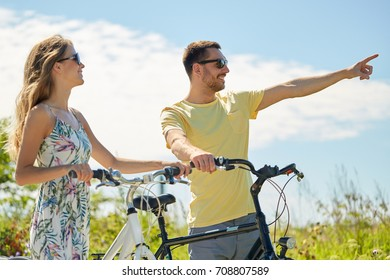 people, direction and lifestyle concept - happy young couple with bicycles at country in summer