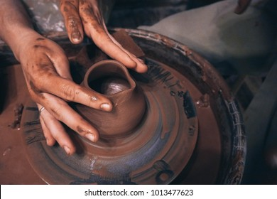 People with dirty hands creates a clay pot milk jug in the pottery workshop