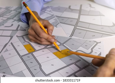 people discussing about territory building plots on cadastral map - Shutterstock ID 1833311719