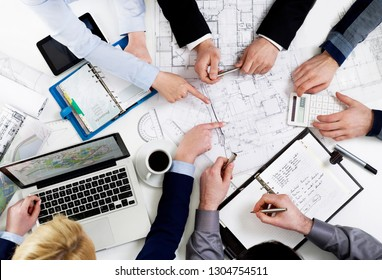People discussing at table over papers