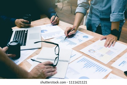 People discussion about graph on desk in office room.