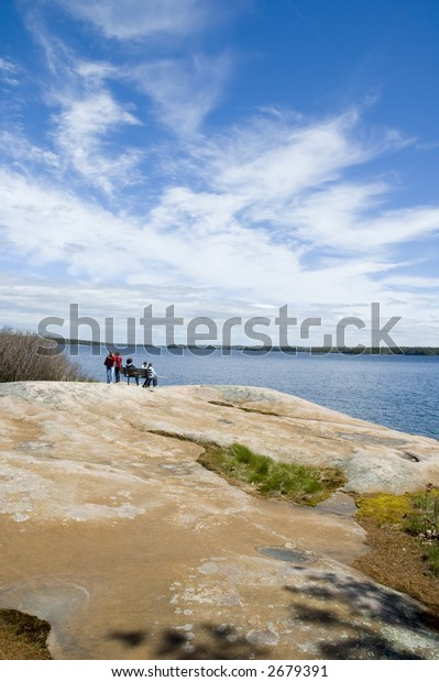 People at distance resting on bench and enjoying view