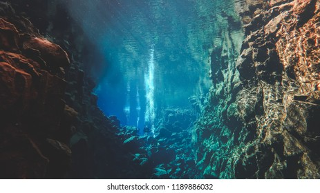 People divers diving in a famous crack between two tectonic plates in Iceland Silfra hall blue deep underwater water colors colorful lava rock formations, crystal clear sky diving floating air bubbles