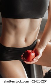People do sport boy drinks water .group of people resting on a workout, in the hands of apples. body parts close up,such as the abdomen, back muscles. to measure the size of the volume of hands.