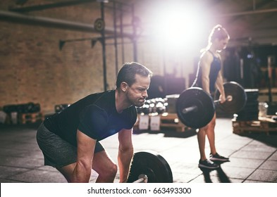 People do workout with barbells in gym. Horizontal indoors shot