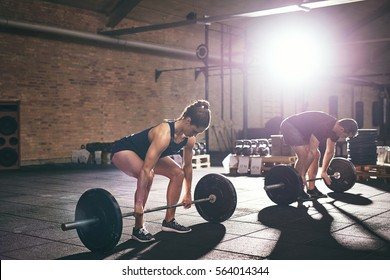 People doing deadlift with heavy barbells in gym. Horizontal indoors shot