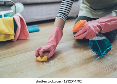 people doing housework and housekeeping concept. close up of woman in rubber gloves with scouring pad cleaning wooden floor at home. lady spraying cleaner on the ground in the living room.