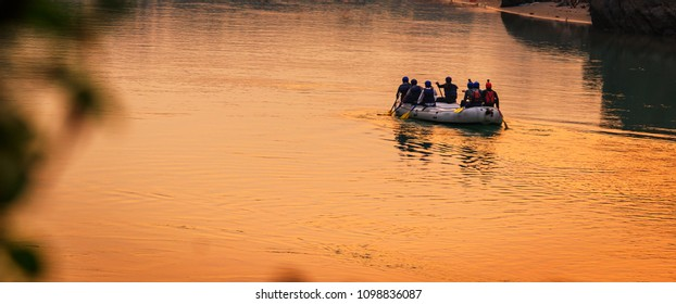 People doing Rafting on the river Ganges in Rishikesh India during sunset