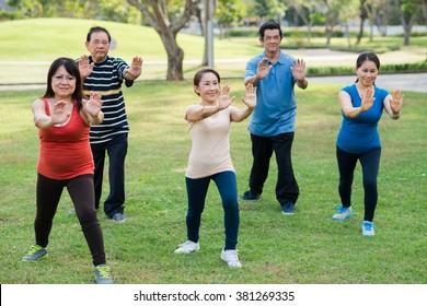 People doing Tai Chi movement: pushing forward