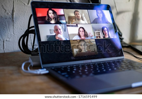People doing a virtual meeting online.  Laptop on work from home desk.  Coworkers in a team meeting during COVID-19 coronavirus pandemic.