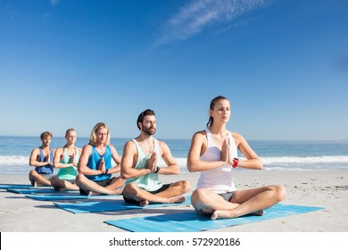 People doing yoga on the beach on a sunny day