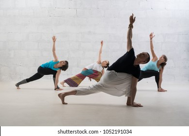 People doing yoga shot against white brick wall